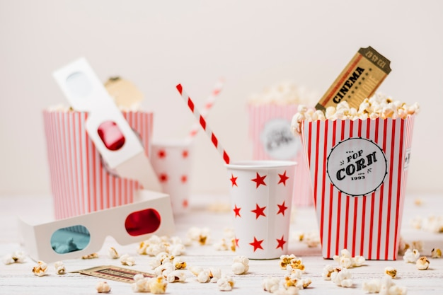 3d glasses; disposable cup with drinking straw; cinema ticket and popcorns Free Photo