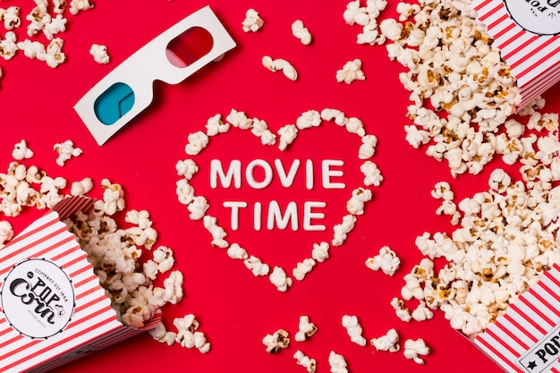 3d glasses; popcorn spilled from box with movie time text in heart shape on red backdrop Free Photo