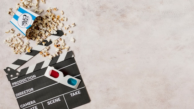 3d glasses with popcorns and clapperboard on concrete backdrop Free Photo