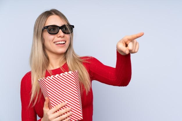 Молодая белокурая женщина над изолированной синей стеной с 3d-очками и держащей большое ведро попкорнов, указывая в сторону Premium Фотографии