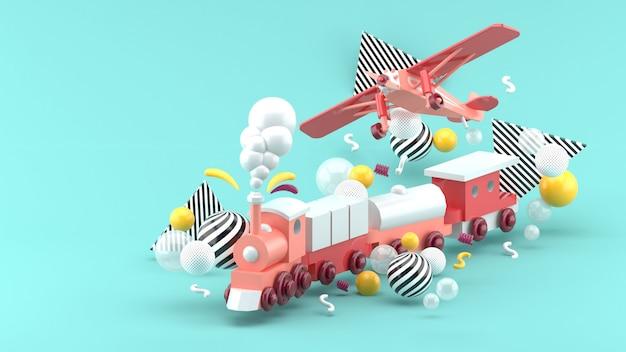 Розовый игрушечный поезд и самолет среди разноцветных шариков на синем. 3d визуализация. Premium Фотографии