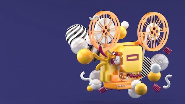 Оранжевый кинопроектор на фоне разноцветных шариков на фиолетовый. 3d визуализация. Premium Фотографии