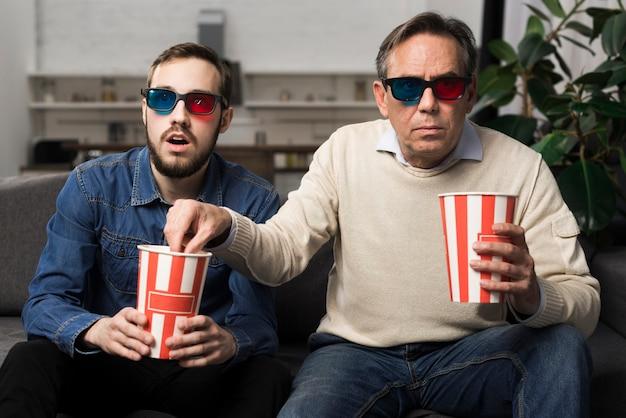 Отец и сын смотрят 3d фильм в гостиной Бесплатные Фотографии