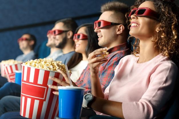 3dで見る。映画館で映画を見ながら一緒に座ってポップコーンを食べている友人 Premium写真