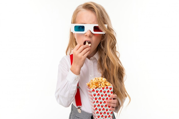3dメガネで長いブロンドの髪を持つ少女はポップコーンを食べます。 Premium写真