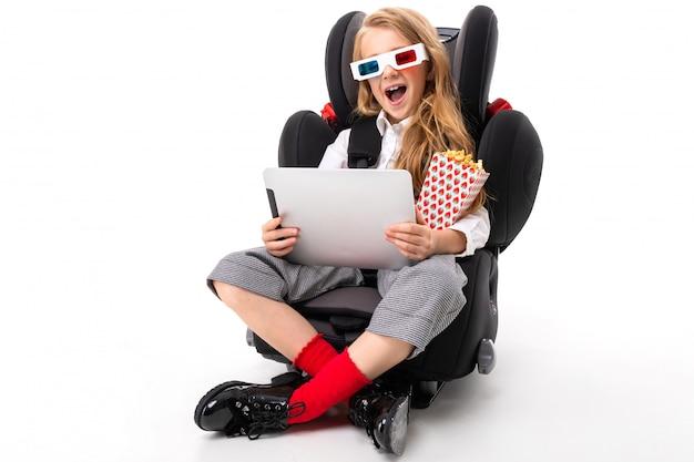 タブレット、イヤホン、ポップコーン、3dメガネ、漫画の面白い映画を見ると車のベビーチェアに座っている化粧と長いブロンドの髪を持つ少女 Premium写真