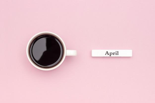木製カレンダー春4月とパステルピンクの紙の背景にブラックコーヒー1杯 Premium写真