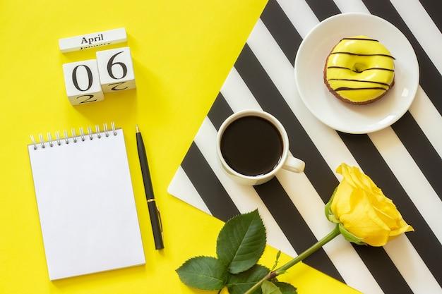 4月6日一杯のコーヒードーナツは、黄色の背景にメモ帳をバラしました。コンセプトスタイリッシュな職場 Premium写真