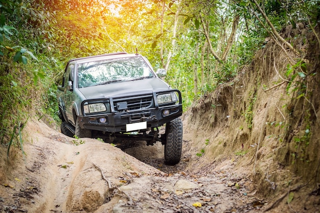 4 wheel drive is climbing on a difficult off-road in mountain forests in thailand. Premium Photo