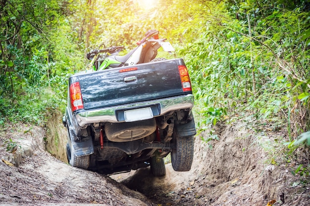 4 wheel drive with a motorcycle on the tailgate is climbing on a difficult off-road. Premium Photo