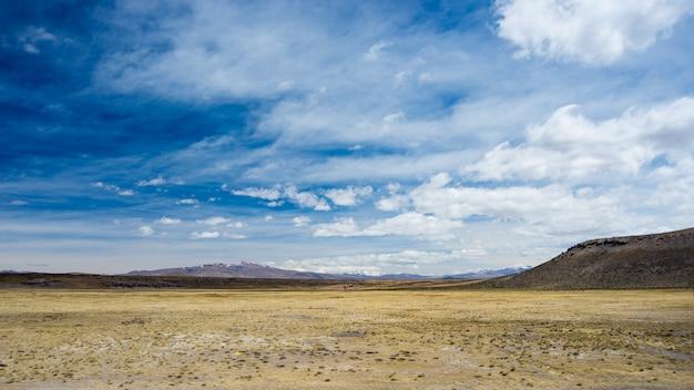 荒れた不毛の風景と風光明媚な劇的な空と高地の風景ペルーアンデス高地の4000 mで上から広角ビュー。 Premium写真