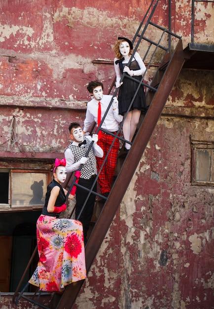 赤い壁の階段に立っている4つのマイム Premium写真
