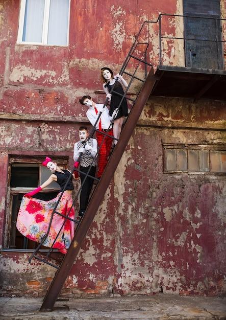 赤い壁の階段の上に立っている4人のマイム。 Premium写真