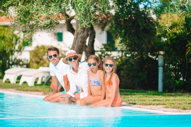 スイミングプールで4人の幸せな家族 Premium写真