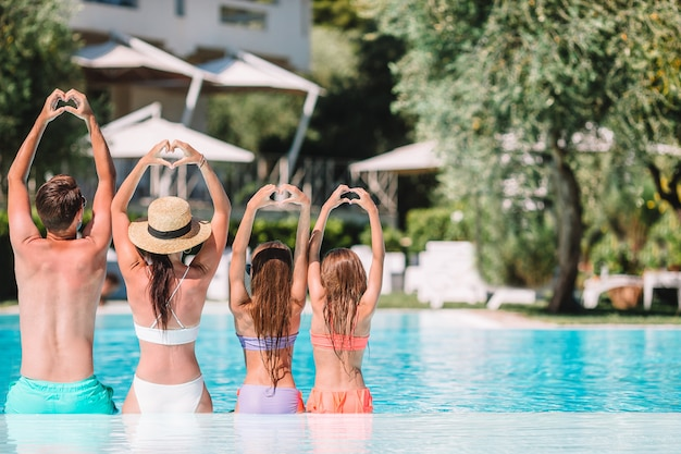 屋外スイミングプールで4人の幸せな家族 Premium写真