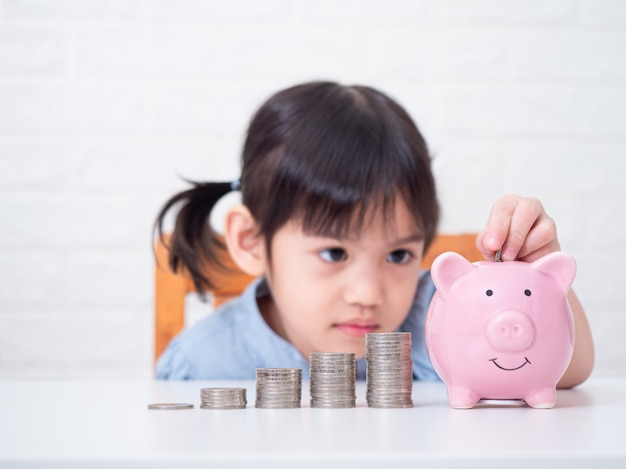 Азиатская маленькая милая девушка 4 лет сбережений денег к розовой свинье на белой стене селективный фокус на монетках. Premium Фотографии