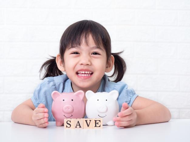 Азиатская маленькая милая девочка 4 лет экономит деньги на розовую свинью на белой стене Premium Фотографии