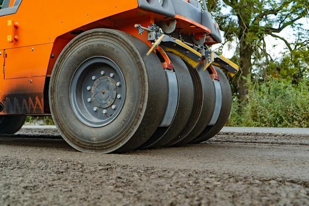 4つの車輪が付いているアスファルトのためのオレンジ色のスチームローラーは、日に道路に立っています。 Premium写真