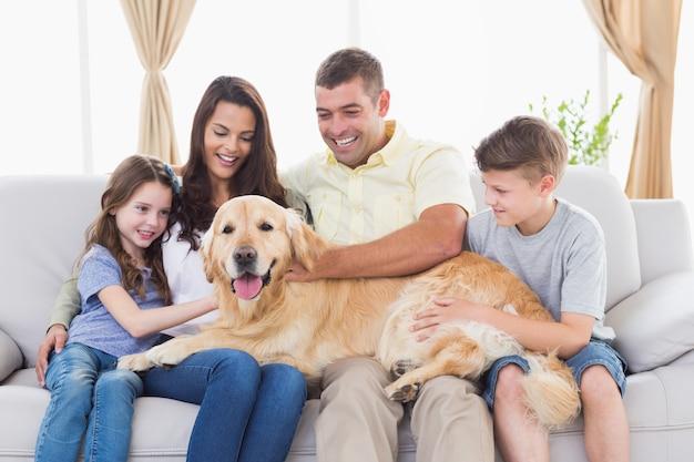 リビングルームのゴールデンレトリーバーの4人の幸せな家族 Premium写真