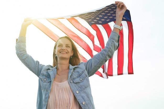 Девушка в коралловом платье и джинсовой куртке держит в руках флаг соединенных штатов. 4 июля день независимости. Premium Фотографии