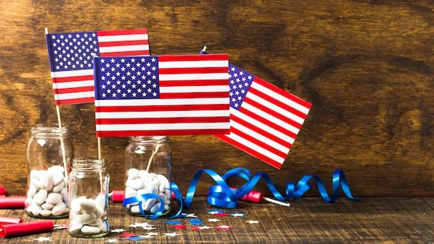 Флаг сша в стеклянной банке с белыми конфетами на деревянный стол для празднования 4 июля Бесплатные Фотографии