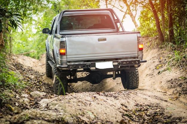 4-х колесный привод поднимается по сложной внедорожью в горных лесах таиланда. Premium Фотографии