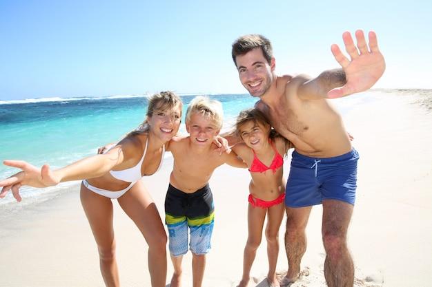 ビーチで楽しんで4人家族 Premium写真