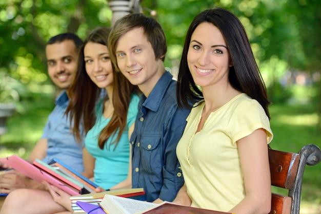 屋外公園で4人の笑顔の陽気な学生。 Premium写真
