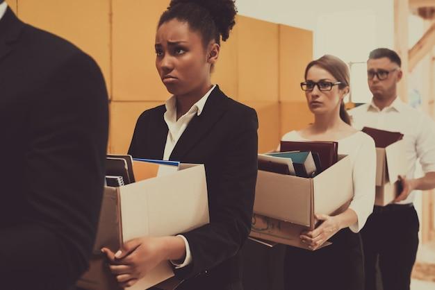 キューの4人のマネージャーが事務所の箱を抱えています。 Premium写真