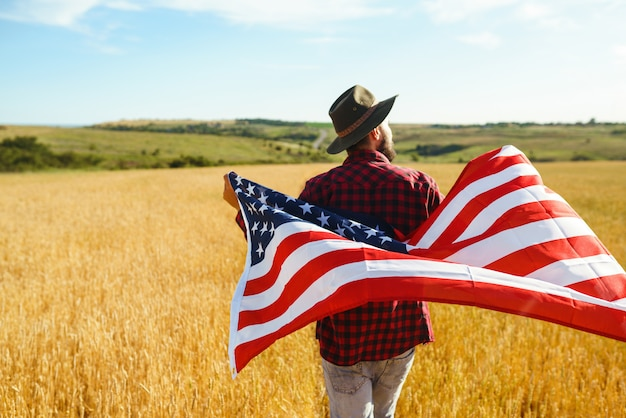 4th of july. fourth of july. american with the national flag. american flag. independence day. patriotic holiday. the man is wearing a hat, a backpack, a shirt and jeans. Premium Photo