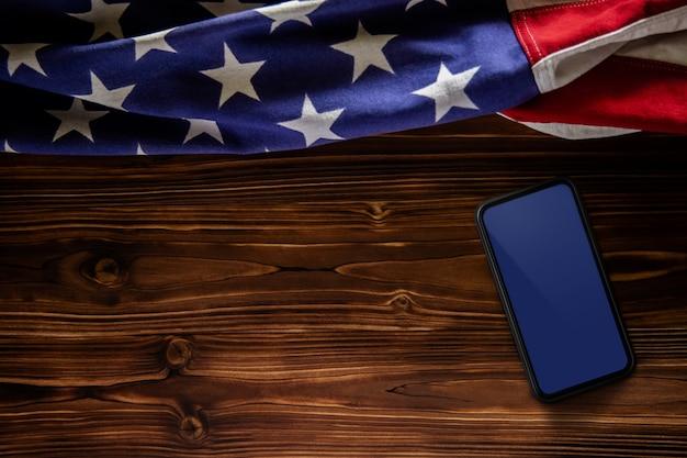4 июля или день поминовения соединенных штатов концепции. пустой мобильный экран для макета. флаг сша, лежа на деревянных фоне. американская символика. вид сверху Premium Фотографии