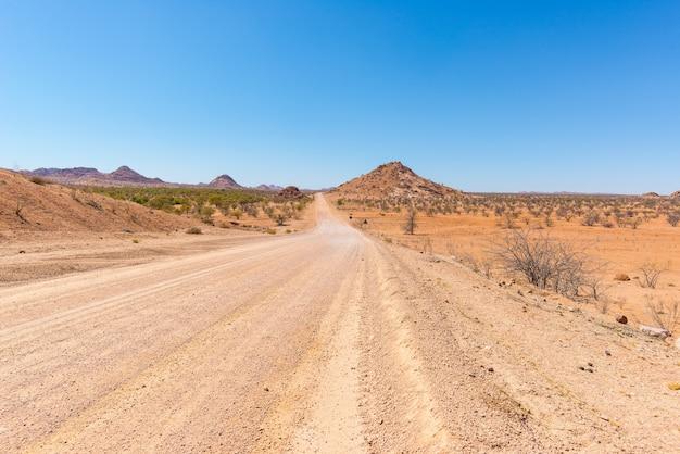 アフリカ、ナミビアの雄大なダマラランドブランドバーグにあるトワイフェルフォンテインのカラフルな砂漠を横断する砂利4x4道路。 Premium写真