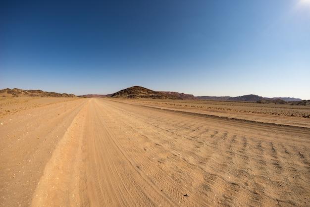 アフリカ、ナミビアの風光明媚な旅行先であるダマラランドブランドバーグのトワイフェルフォンテインでカラフルな砂漠を横断する砂利4x4道路。 Premium写真