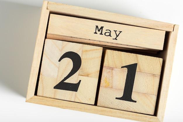 白の日付を持つ木製キューブ。 5月21日 Premium写真