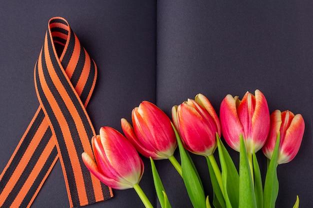 5月9日のテンプレート空白のグリーティングカード。赤い花(チューリップ)、黒いノートにジョージのリボン。戦勝記念日または祖国の擁護者の日の概念。トップビュー、テキストのコピースペース Premium写真