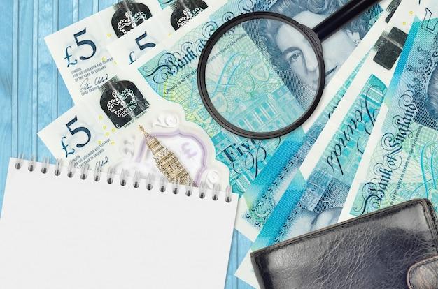 5ポンドの紙幣と黒い財布とメモ帳付きの虫眼鏡。偽造お金の概念。 Premium写真