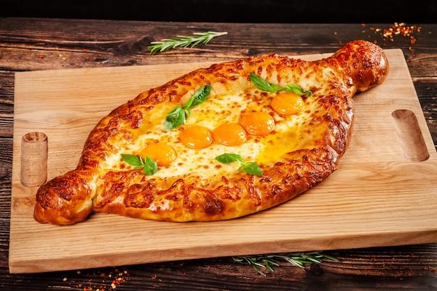 グルジア料理。木の板に、卵黄5個の大きなkhachapuri。大企業向けのレストランでの料理。背景画像のコピースペース Premium写真