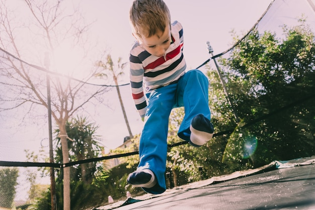 5 year old boy jumping on a trampoline enjoying his energy, face with expressions of happiness to play outdoors. Premium Photo