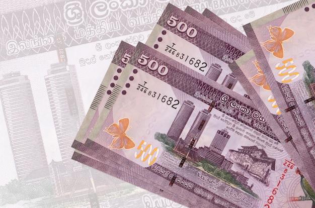 Банкноты 500 шри-ланкийских рупий лежат в стопке на фоне большой полупрозрачной банкноты. Premium Фотографии