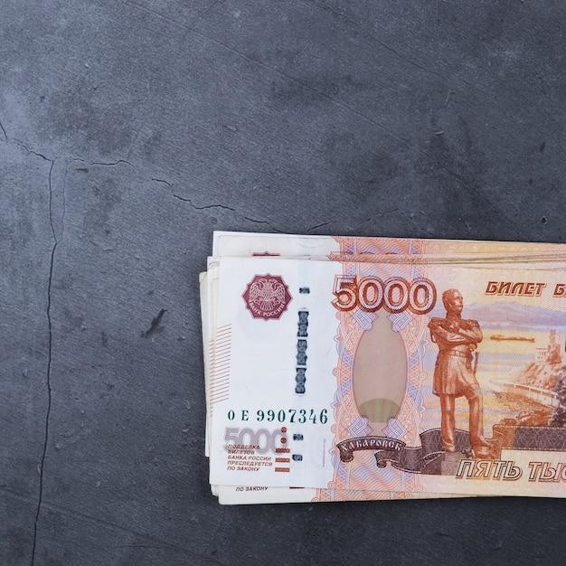 灰色のセメントの上に横たわる5000ルーブルのロシアのお金紙幣のビッグスタック。 Premium写真
