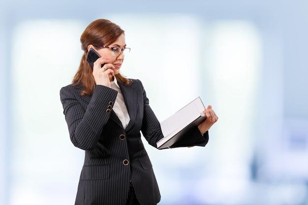 Портрет красивой коммерсантки 50 ушей старых с мобильным телефоном в офисе. Premium Фотографии