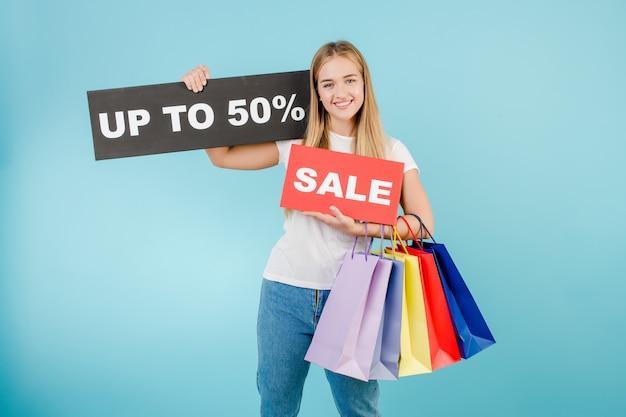 幸せな笑みを浮かべてきれいな女性販売最大50%記号と青で分離されたカラフルなショッピングバッグ Premium写真