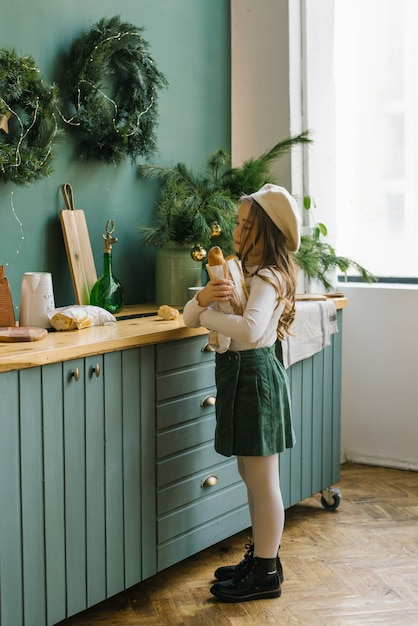 白と緑の花のおしゃれな服を着た5歳の少女は、クリスマスの装飾が施されたキッチンの近くに立って、バゲットと紙袋を保持しています。 Premium写真