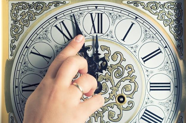 女性は5から真夜中を示す古いビンテージ時計に指を向けた。 Premium写真