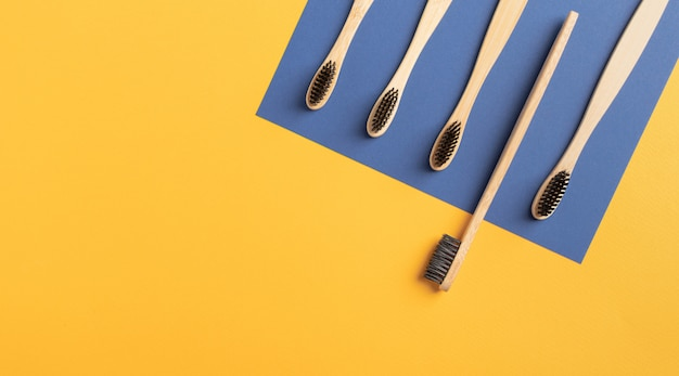 竹歯ブラシは、黄色と青の背景に5個のクローズアップ。黒い火山カーボン歯ブラシフラットコピースペースを置く。医学、環境に優しい、廃棄物ゼロのコンセプト。 Premium写真
