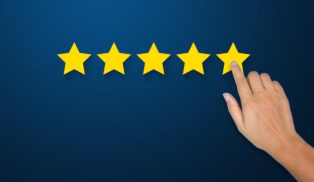 会社の概念の評価を高めるために5つ星のシンボルに触れる実業家の手 Premium写真