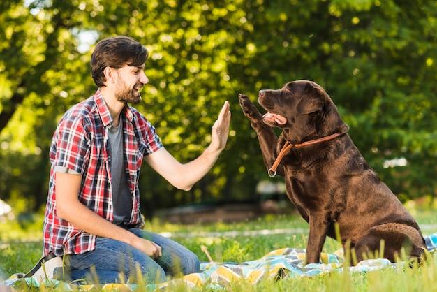 公園で彼の犬に最高5を与える若い男 無料写真