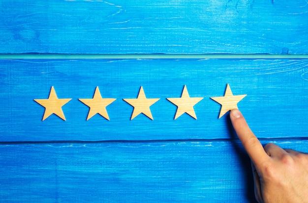 女性の手が5番目の星を置きます。品質ステータスは五つ星です。新しいスター、成果 Premium写真