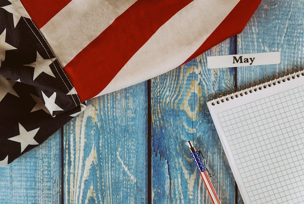カレンダー年の5月月アメリカ合衆国のメモ帳とオフィスの木製テーブルの上のペンで自由と民主主義のシンボルのアメリカ合衆国の旗 Premium写真