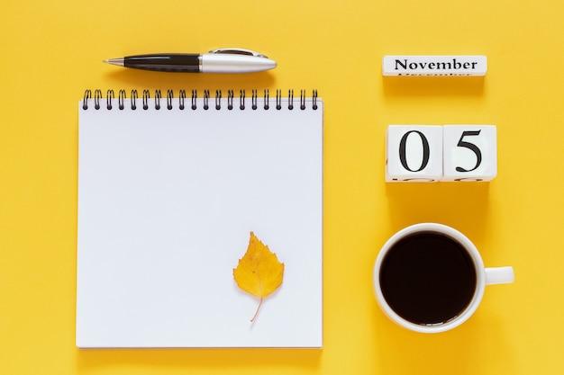 5 ноября чашка кофе, блокнот с ручкой и желтый лист на желтом Premium Фотографии